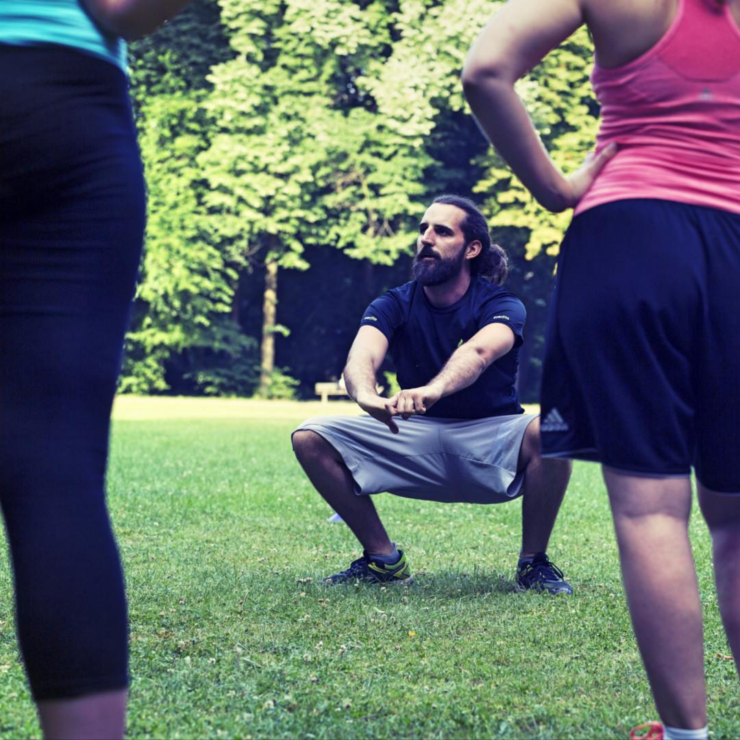 Personal Trainer macht beim everfits Outdoor Training die Kniebeuge vor