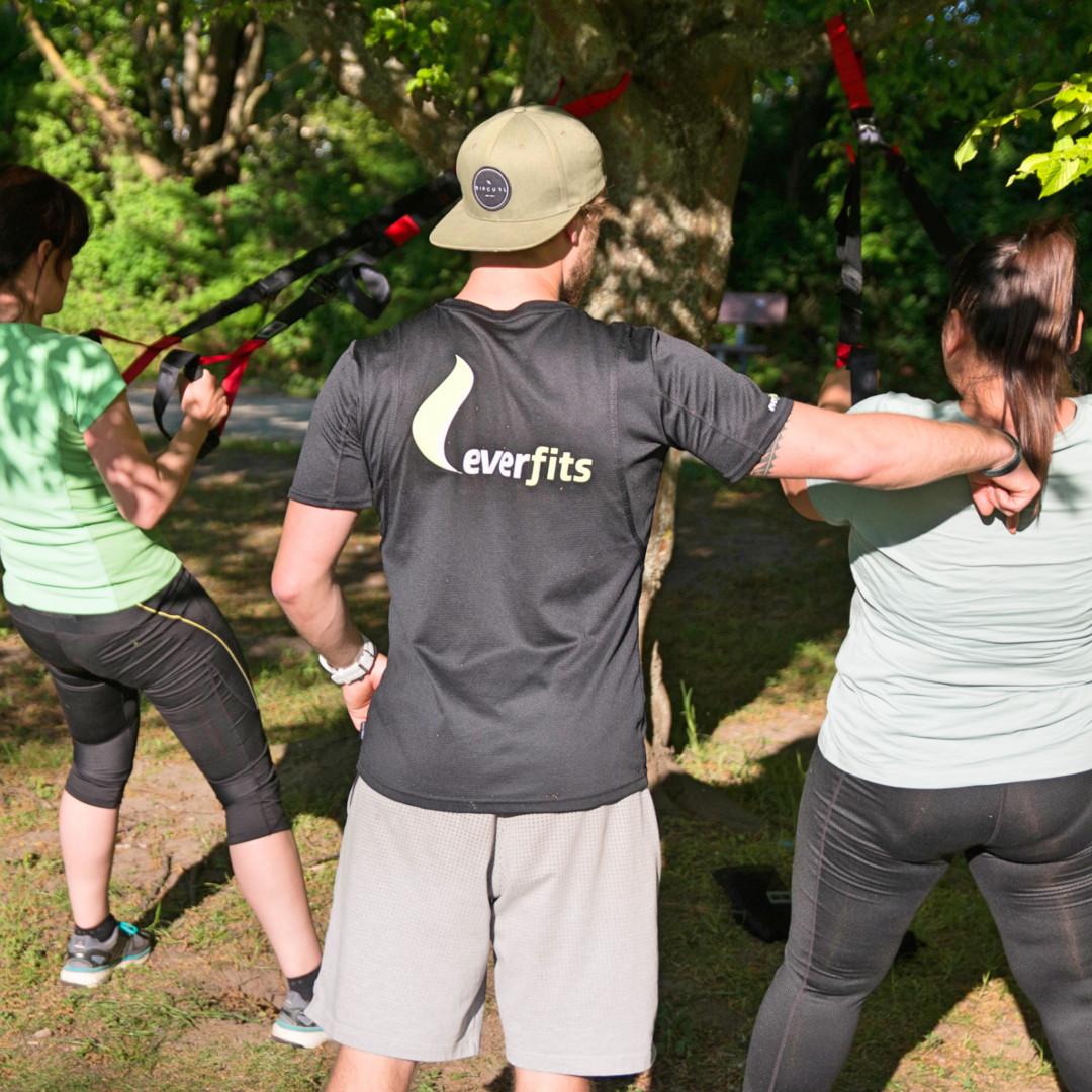Fitness Trainer korrigiert beim Outdoor Training die Ausführung der Übung Rudern mit dem Slingtrainer